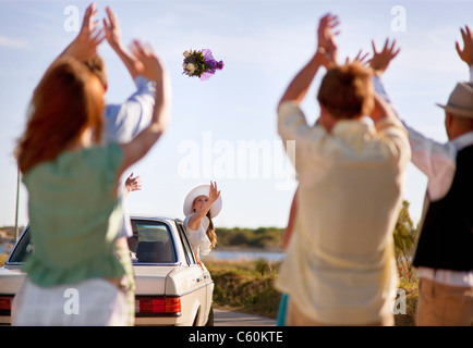 Bride throwing bouquet from car - Stock Photo
