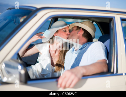 Newlywed couple kissing in car - Stock Photo