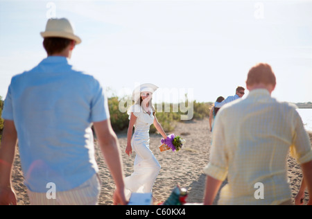 Bride walking with friends on beach - Stock Photo