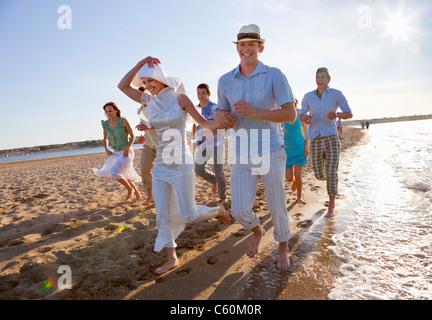 Newlywed couple on beach with friends - Stock Photo