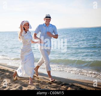 Newlywed couple running on beach - Stock Photo