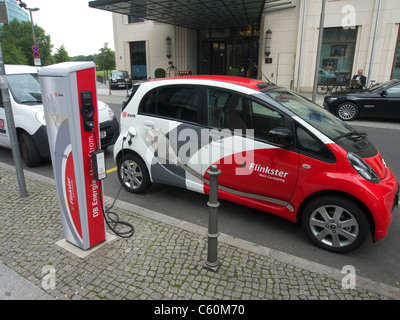 Flinkster DB carsharing electric car being recharged on street in Berlin Germany - Stock Photo