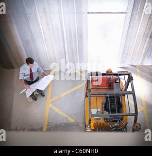 Businessman reading blueprints on site - Stock Photo