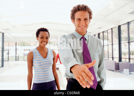 Businessman extending hand in greeting - Stock Photo