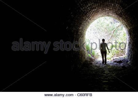 Woman walking in tunnel - Stock Photo