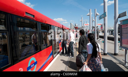 Passengers boarding a DLR Docklands Light Railway train carriage at Poplar, East London UK - Stock Photo