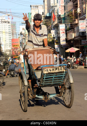 Vietnamese tricycle rickshaw driver calls for a fare in Ho Chi Min city Vietnam - Stock Photo