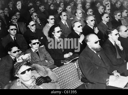 British audience wears smoke-colored glasses to view a 3-D movie in 1954. - Stock Photo