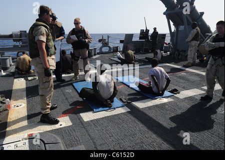 U.S. Sailors guard suspected pirates on the flight deck of the guided missile cruiser USS Gettysburg in the Gulf - Stock Photo