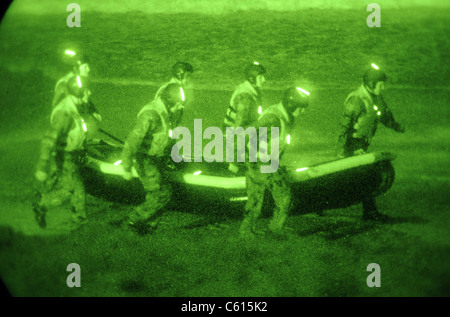 US Sailors assigned to Basic Underwater Demolition/SEAL training class carry an inflatable boat toward the surf - Stock Photo