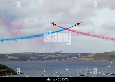 Two Red Arrows jets crossing over in an air display above Falmouth, Cornwall UK - Stock Photo