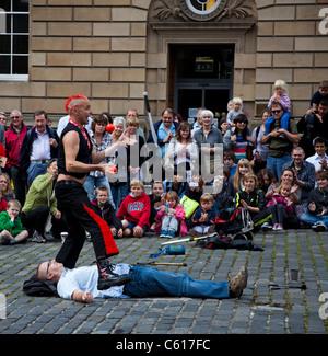 Mighty Gareth Edinburgh Fringe Festival Street Performer juggling knive and balls above volunteer 2011 - Stock Photo