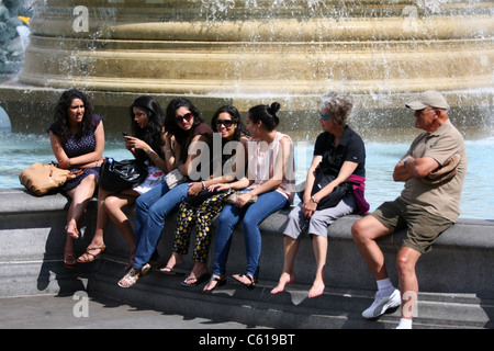 a group of girls sitting on the side of a fountain in Trafalgar Square enjoying themselves with two older people - Stock Photo