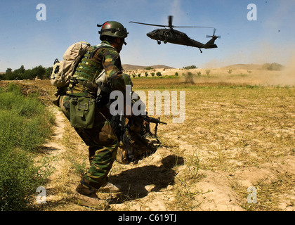 An Afghan commando braces himself as a UH-60 Black Hawk helicopter comes in to extract him following a clearing - Stock Photo