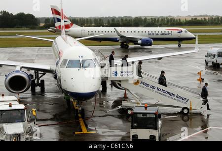 BA Cityflyer Embraer aircraft on the apron at Edinburgh Airport Scotland Passengers disembarking British Airways - Stock Photo