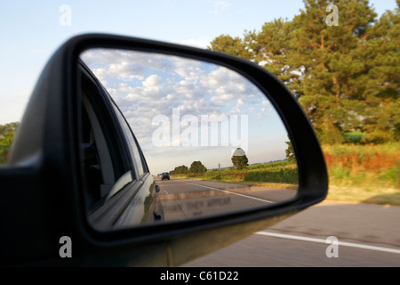car wing side mirror showing cloudy sky while driving along a highway in the usa - Stock Photo