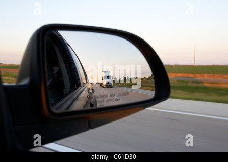 car wing side mirror showing rear view and semi truck while driving along a highway in the usa - Stock Photo