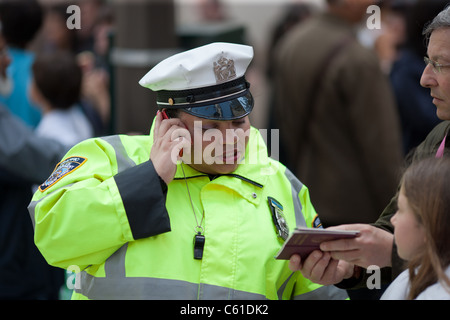 A New York City Traffic Enforcement officer assists a tourist on 5th Avenue in New York City. - Stock Photo