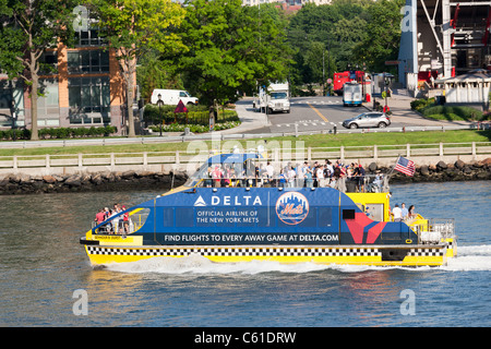 The Delta Baseball Water Taxi passes Roosevelt Island carrying passengers to a NY Mets game in New York City. - Stock Photo