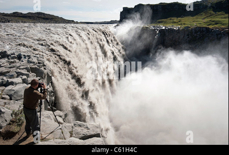 photographer taking picture of largest waterfall in Europe - Dettifoss from close distance, Iceland - Stock Photo