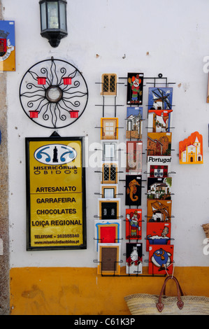 Postcard rack and chocolate shop sign in the medieval town of Obidos some 50 miles north of Lisbon, Portugal - Stock Photo