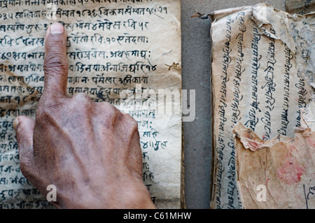 A man trying to read an old manuscript written in Nepali - Stock Photo