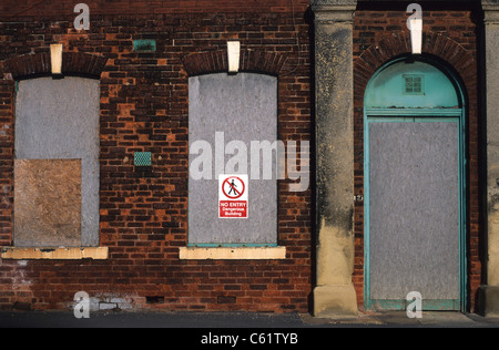 no entry warning sign on boarded up and derelict building in Leeds UK - Stock Photo