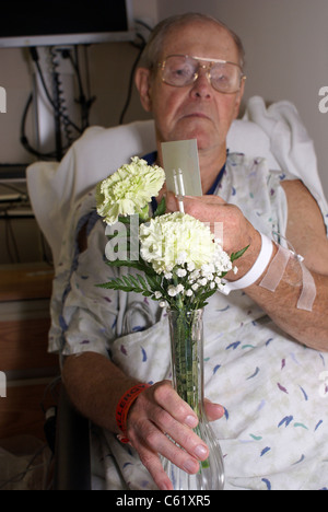 Hospital patient holding gift flowers. - Stock Photo