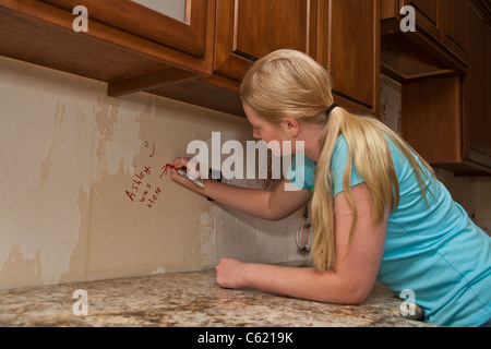 Teen girl writing on unfinished areas of kitchen remodel. MR Myrleen Pearson - Stock Photo