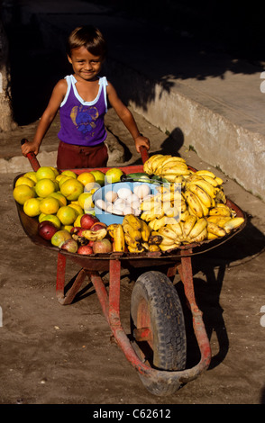 small smiling mexican boy with a whellbarrow ful of fruits for sale. Sweet - Stock Photo