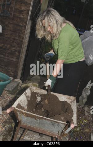 woman using spade to move soil from wheelbarrow to tubs - Stock Photo