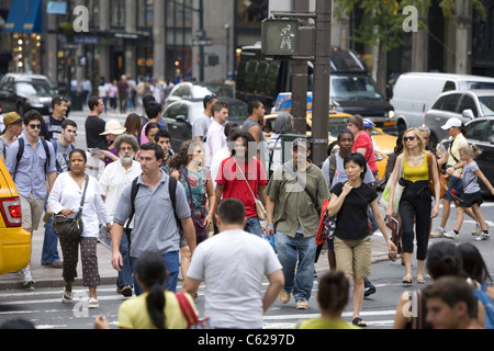 The street is always crowded with tourists, New Yorkers and workers at 5th Avenue and 42nd Street in New York City. - Stock Photo