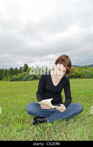 Reading on the meadow - Stock Photo