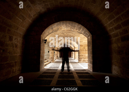 Man standing in dark tunnel under Palma Mallorca Cathedral. Ancient buildings with arms held out. - Stock Photo