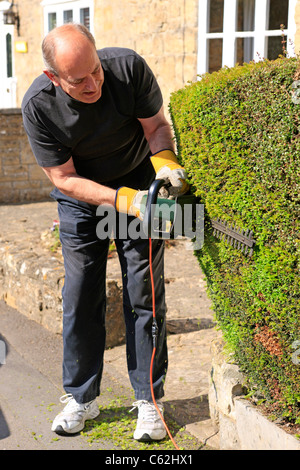 A senior man using an electric hedge trimmer - Stock Photo