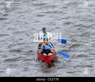 Two seniors man and woman couple paddling a canoe. - Stock Photo