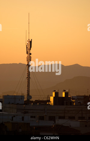 Radio and mobile phone mast in Granada, Spain, at sunset. - Stock Photo