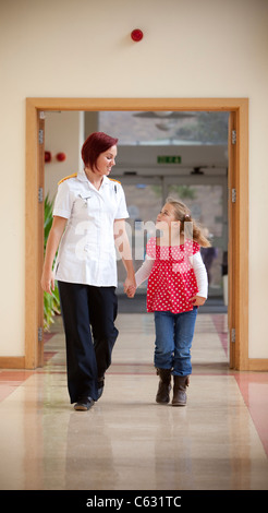A young female nurse walking hand in hand with a young girl patient on a hospital corridor. - Stock Photo