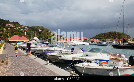 Children pass boats at the waterfront in Gustavia in St. Barts, with the Anglican/Episcopal Church in the background - Stock Photo