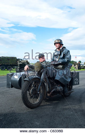 two men dressed as a world war ii German soldier riding a motor bike, at a re enactment and nostalgia weekend at - Stock Photo