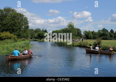Families boating in wooden rowing boats on the River Stour near Dedham, Essex and Suffolk, England. - Stock Photo