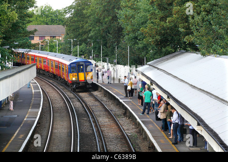 Commuters waiting for the morning train at Mortlake, London - Stock Photo
