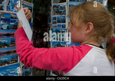 Young girl looking at postcards on a display in Chamonix Mont Blanc, France. - Stock Photo