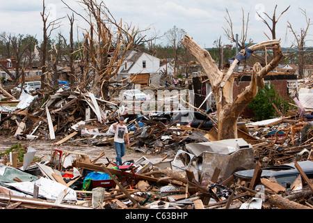 A man walks through the mangled debris of a residential neighborhood in Joplin, Missouri, May 25, 2011. - Stock Photo