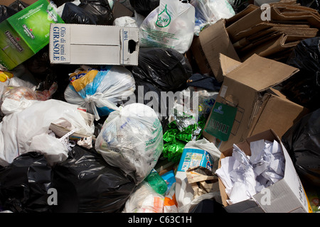 While the garbage men go on strike, the trash piles up in the streets of Naples, Italy, with plastic bags and cardboard - Stock Photo