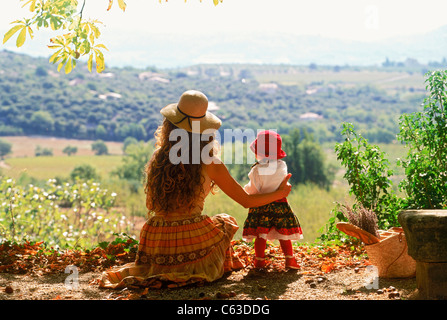 Mother and child resting on roadside in Provence wearing traditional local French dresses - Stock Photo