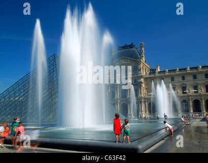 Children next to fountains at Louvre Palace Museum in Paris - Stock Photo