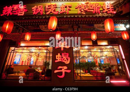 Neon signs and red lanterns at night  illuminating menu at Chinese restaurant in Beijing China - Stock Photo