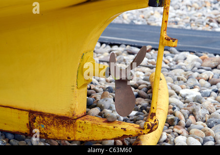 Yellow fishing boat showing the propeller and part of the rudder. - Stock Photo