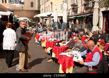 street musician playing guitar in front of a cafe on Campo de Fiori in Rome, Italy - Stock Photo